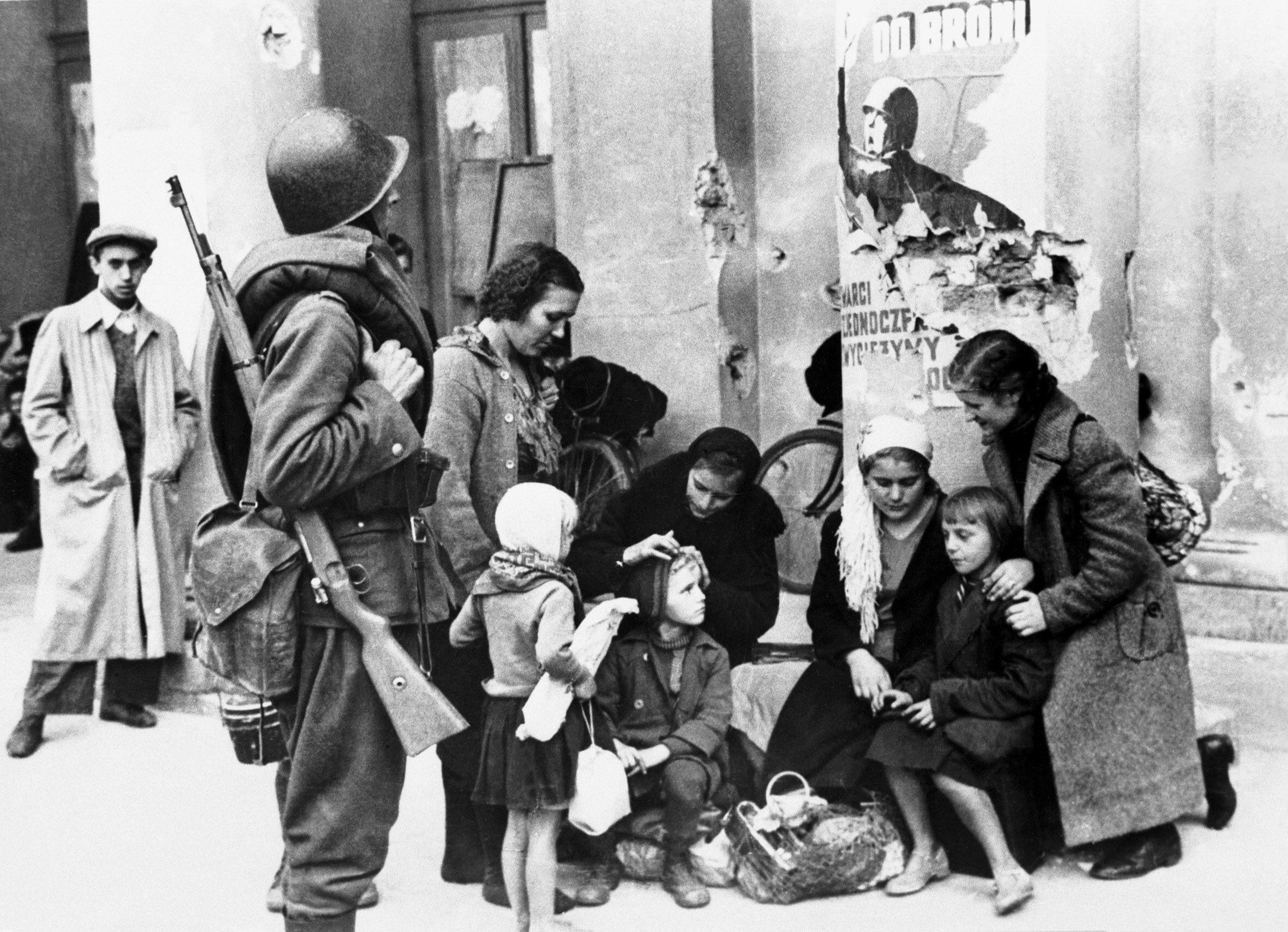 Uciekinierzy w oblężonej Warszawie Polski żołnierz i rodzina, która uciekła przed Niemcami, przy kolumnie Opery w oblężonej Warszawie. Fotografia Juliena Bryana.